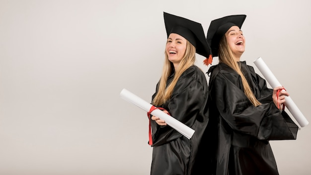 Medium shot graduates laughing with copy space Free Photo