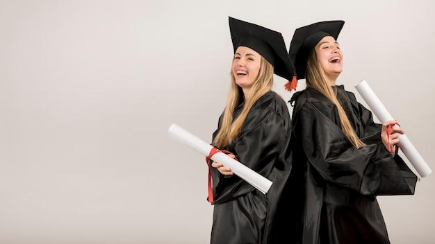 Medium shot graduates laughing with copy space Premium Photo