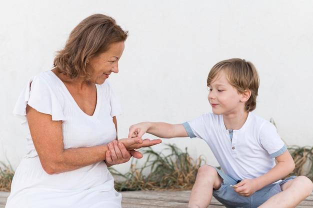 Nonna e bambino con conchiglie a tiro medio Foto Gratuite
