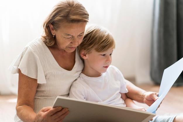 Medium shot grandmother reading book Free Photo