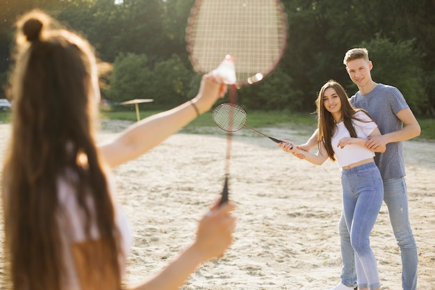 Medium shot group of friends playing badminton Free Photo