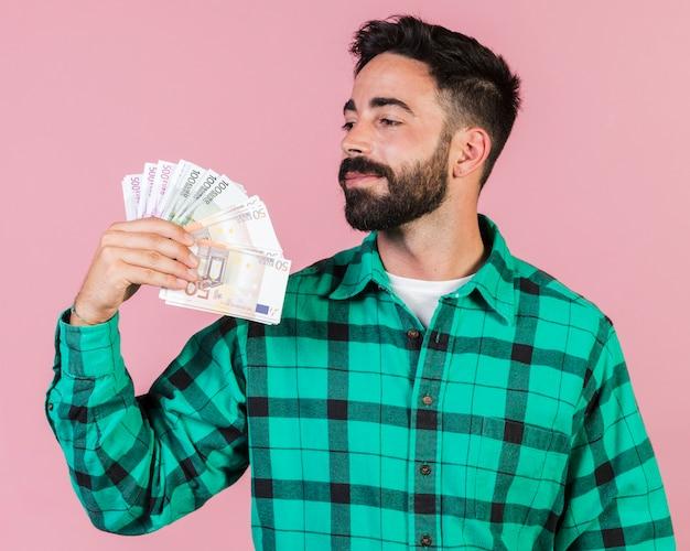 Medium shot guy holding money Free Photo