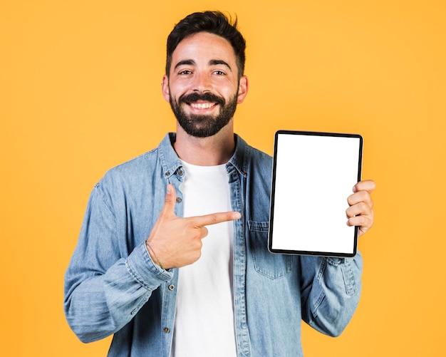 Medium shot guy pointing at a tablet Free Photo