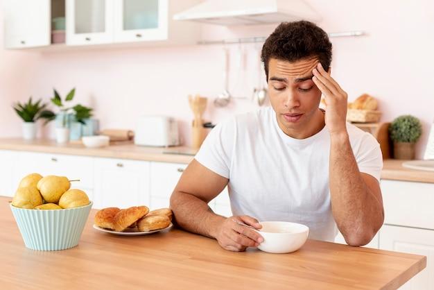 Ragazzo di tiro medio con ciotola di cereali in cucina Foto Gratuite