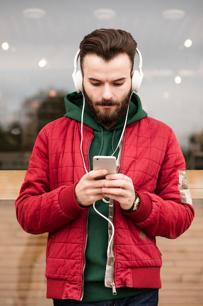 Medium shot guy with headphones looking at smartphone Free Photo
