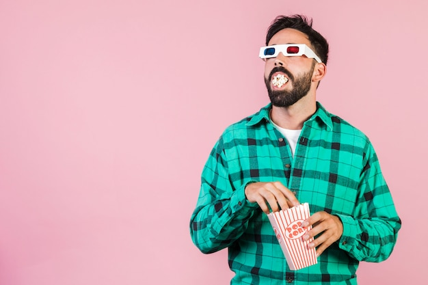 Medium shot guy with mouth full of popcorn Free Photo