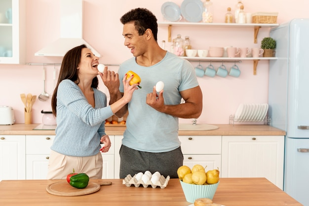 Medium shot happy couple cooking together Free Photo