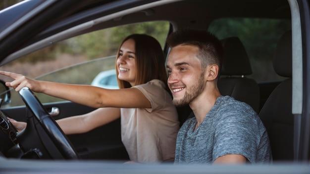 Средний снимок счастливая пара в машине Бесплатные Фотографии