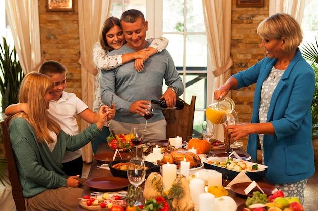 Medium shot happy family at dinner Premium Photo