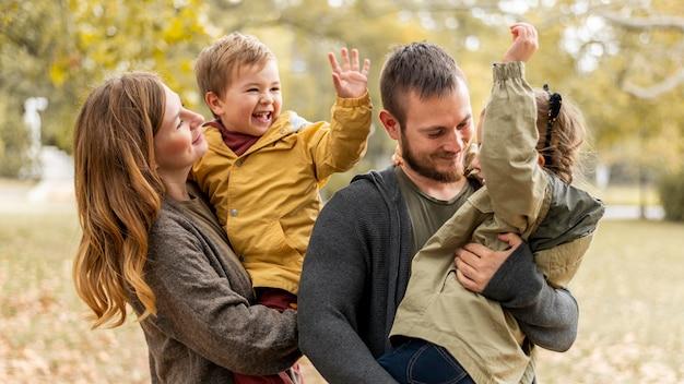 Средний план счастливая семья на открытом воздухе Premium Фотографии