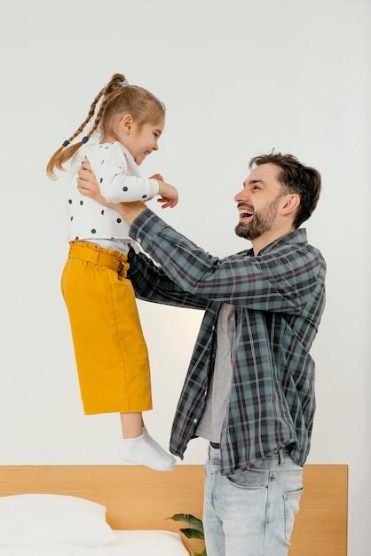 Средний снимок счастливый отец, держащий ребенка Бесплатные Фотографии
