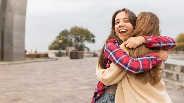 Medium shot happy friends hugging outside Free Photo