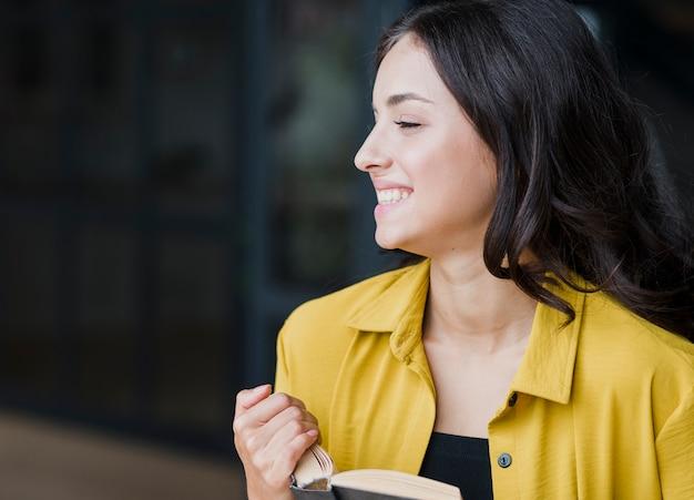 Medium shot happy girl with book Free Photo