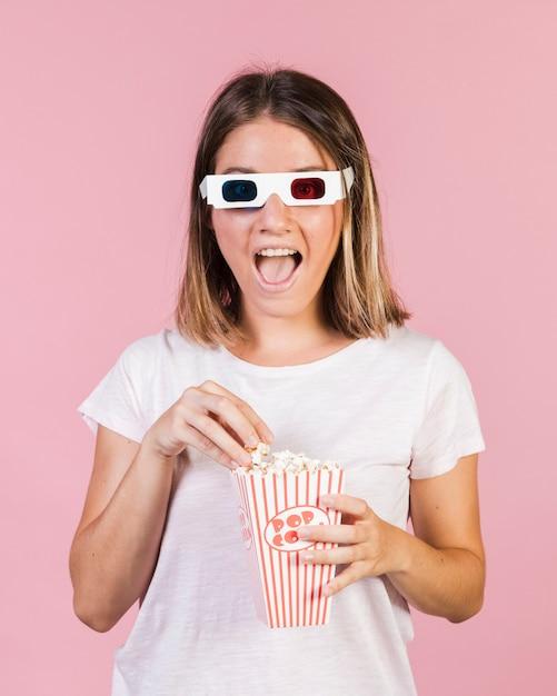 Medium shot happy girl with popcorn Free Photo