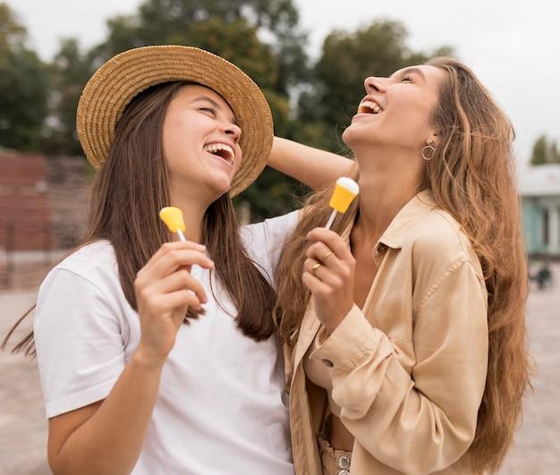 Ragazze felici del colpo medio con la caramella Foto Gratuite