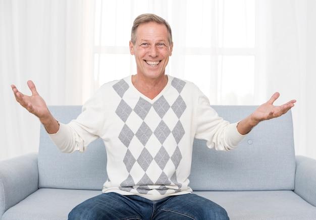 Medium shot happy man sitting on the couch Free Photo