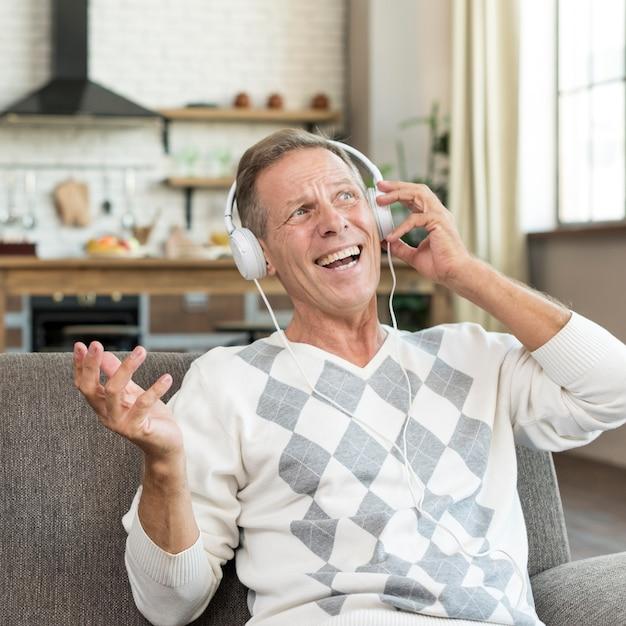 Uomo felice del colpo medio con le cuffie all'interno Foto Gratuite