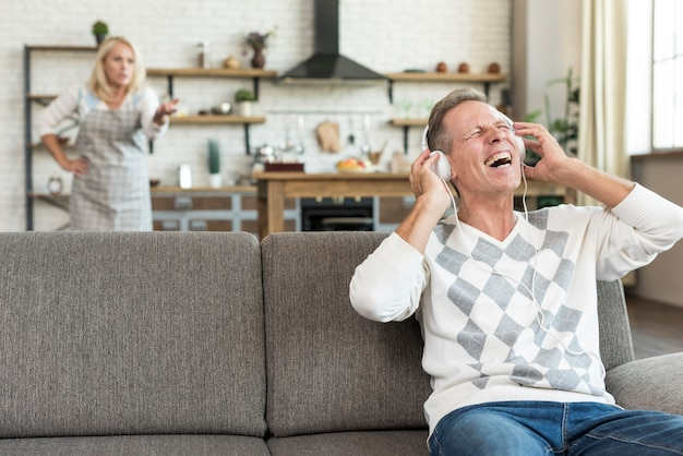 Средний снимок счастливый человек с наушниками на диване Бесплатные Фотографии