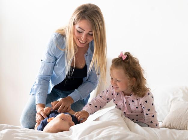ミディアムショット幸せな母の子供たちと遊ぶ 無料写真