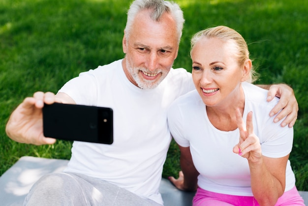 Medium shot happy people taking selfies outdoors Free Photo