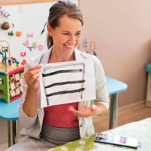 Insegnante felice del colpo medio che tiene pittura Foto Gratuite