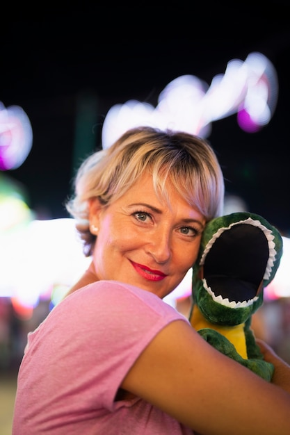 Medium shot happy woman hugging dinosaur toy Free Photo