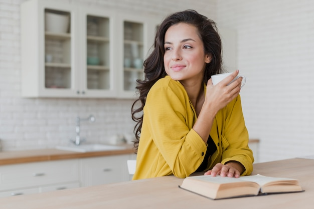 Medium shot happy woman with book looking away Free Photo