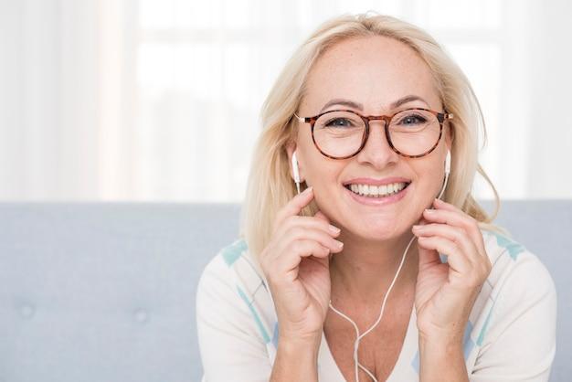 Medium shot happy woman with glasses and headphones Free Photo