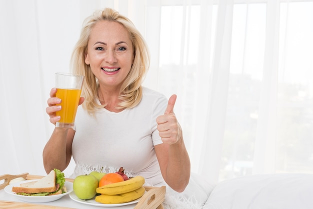 Medium shot happy woman with orange juice showing approval Free Photo