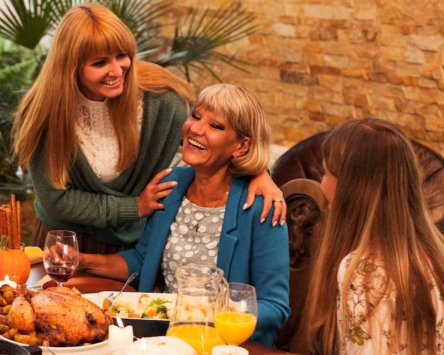 ミディアムショットのディナーテーブルで幸せな女性 無料写真