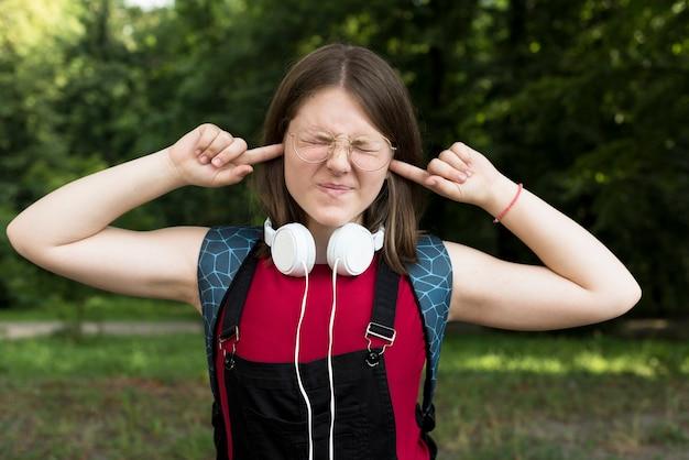 Medium shot of highschool girl covering her ears Free Photo