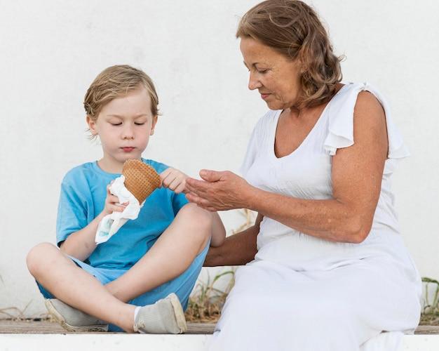 Ragazzo di tiro medio che mangia il gelato Foto Gratuite