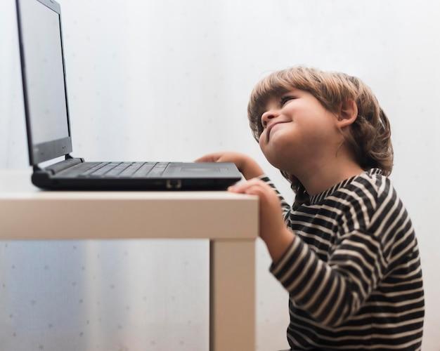 Bambino del colpo medio che esamina computer portatile Foto Gratuite