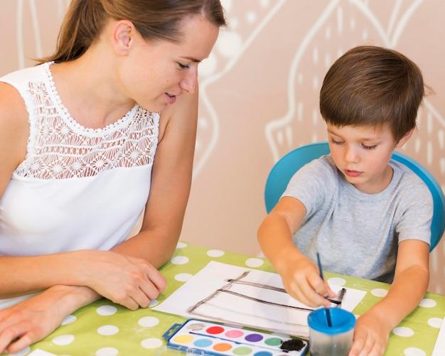 テーブルでミディアムショットの子供絵画 無料写真