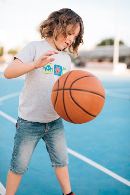 Medium shot of kid playing basketball Free Photo