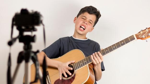 Medium shot kid playing guitar Free Photo