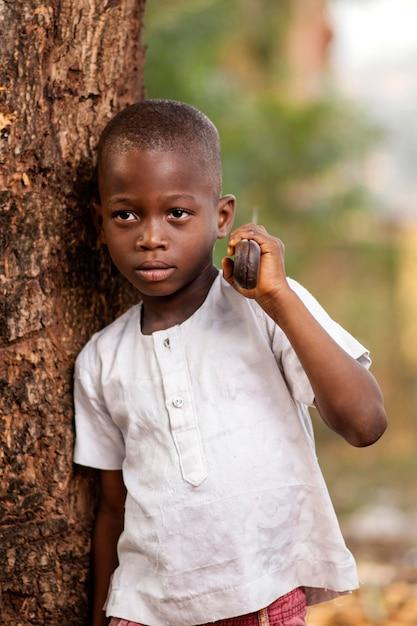 木の近くでポーズをとるミディアムショットの子供 Premium写真