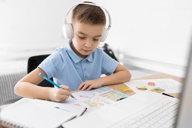 Малыш среднего кадра с рисунком в наушниках Бесплатные Фотографии