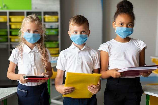 I bambini dal tiro medio tornano a scuola in tempo di pandemia Foto Gratuite