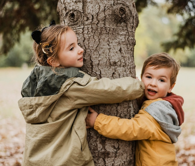 Medium shot kids hugging tree Free Photo
