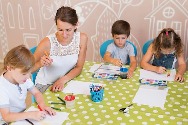 テーブルで絵を描くミディアムショットの子供 無料写真