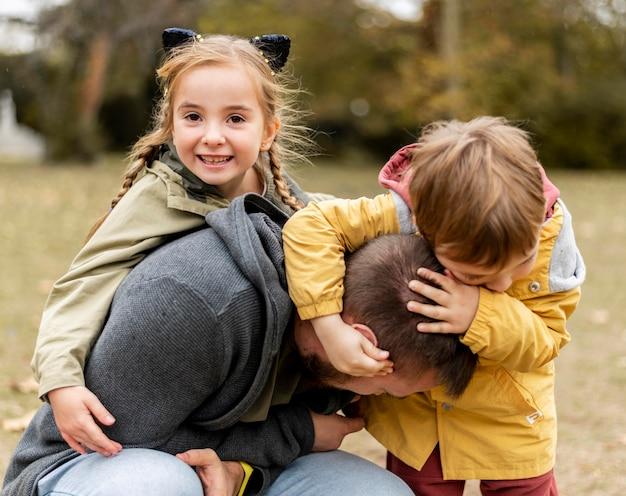 Дети среднего выстрела, играющие с отцом Premium Фотографии