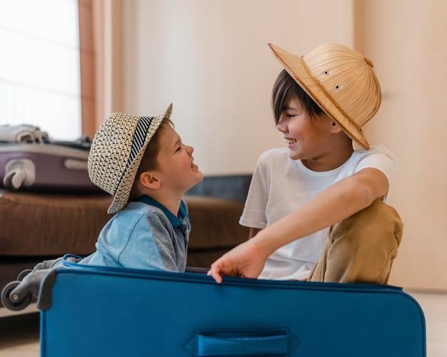 Bambini di tiro medio seduti nel bagaglio Foto Gratuite