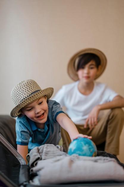 Bambini a tiro medio con globo del mondo Foto Gratuite