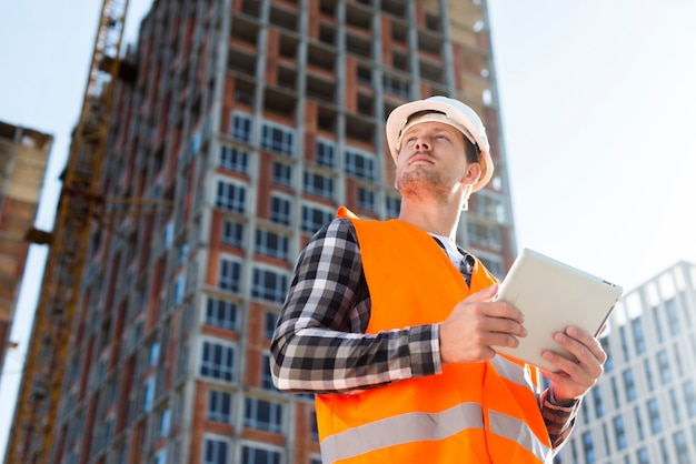 Medium shot low angle view of engineer holding tablet Premium Photo