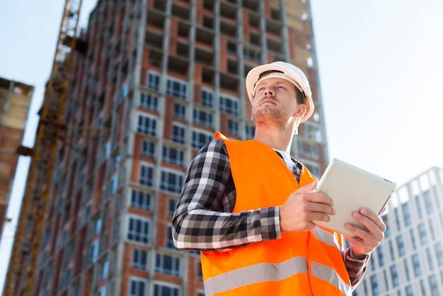 タブレットを保持しているエンジニアのミディアムショットローアングル Premium写真