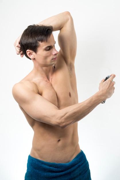 Medium shot man applying deodorant Free Photo