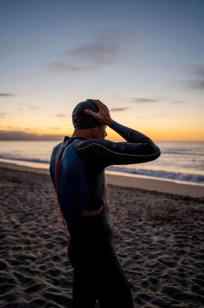 Uomo del colpo medio sulla spiaggia al tramonto Foto Gratuite