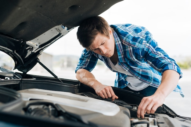 Medium shot of man checking engine | Free Photo