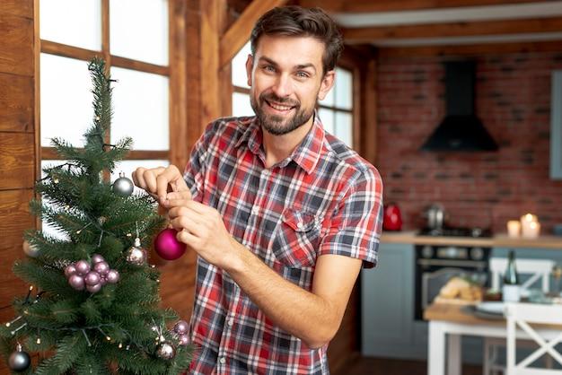 Medium shot man decorating the christmas tree with pink balls Free Photo